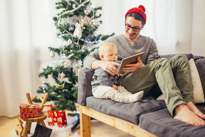 Pai e filho felizes com o computador do PC da tabuleta que joga em casa fotos de stock