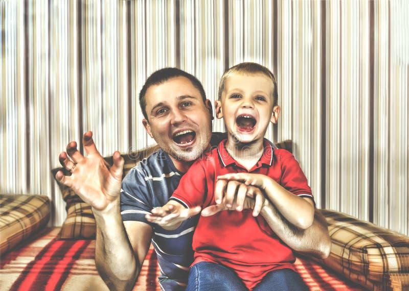 Pai e filho felizes de Dia das Bruxas com dentes do vampiro imagem de stock royalty free