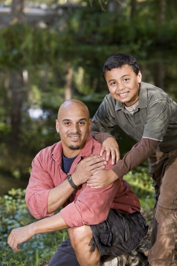 Pai e filho latino-americanos do retrato ao ar livre pela lagoa fotos de stock royalty free