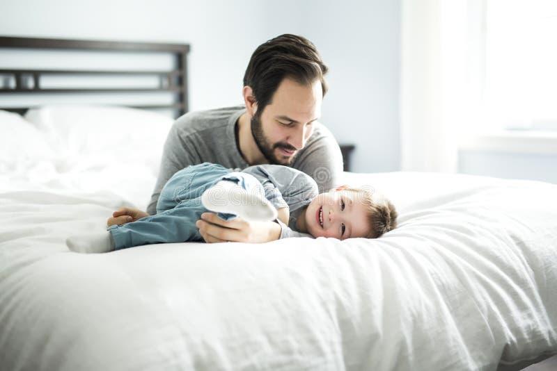 Pai e filho na cama, tempo feliz na cama fotografia de stock