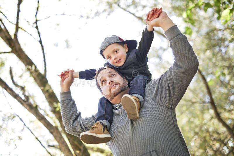 Pai e filho na floresta em um prado fotografia de stock