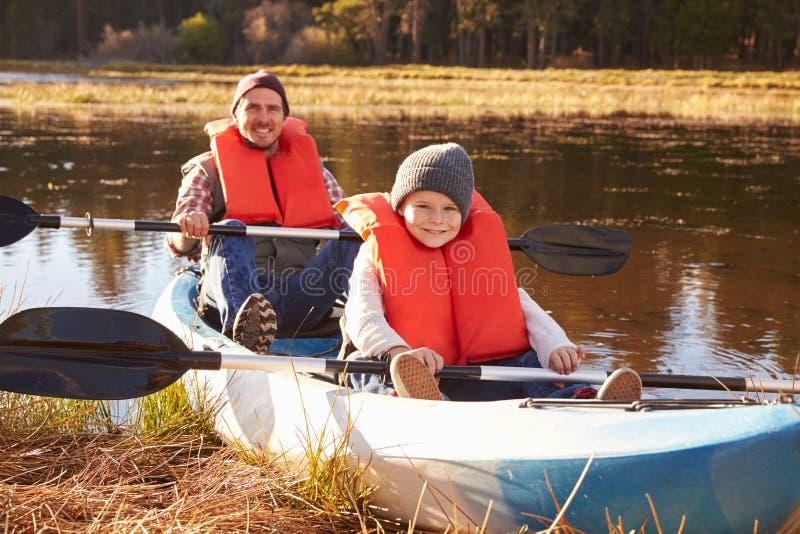 Pai e filho no caiaque na beira do lago, Big Bear, Califórnia imagem de stock