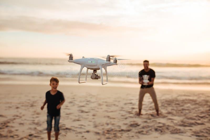 Pai e filho no zangão do voo das férias de verão na praia fotografia de stock