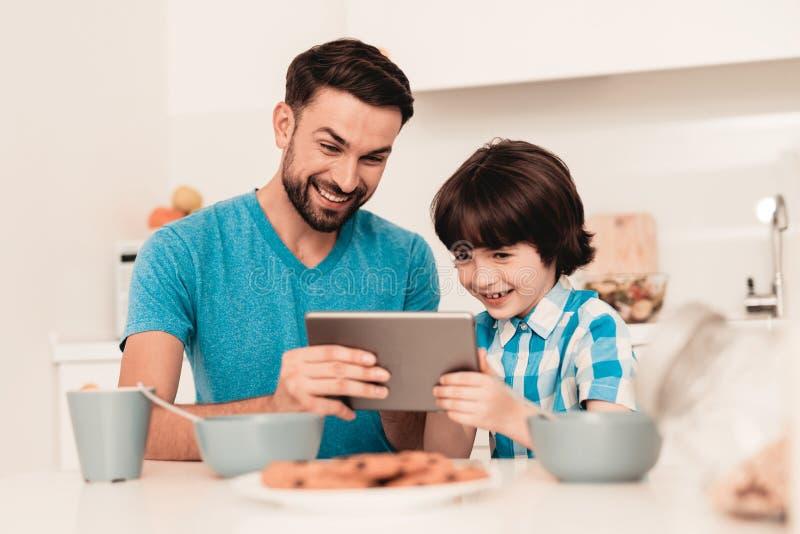 Pai e filho novos felizes que usa a tabuleta em casa imagem de stock royalty free