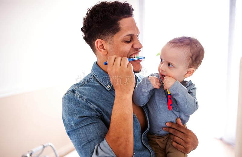 Pai e filho pequeno da criança em um banheiro dentro em casa, escovando os dentes foto de stock