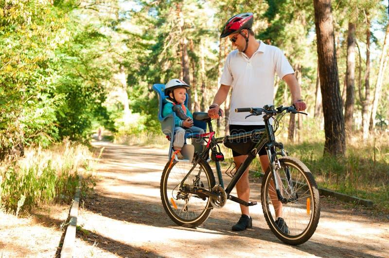 Pai e filho pequeno na bicicleta fotografia de stock royalty free