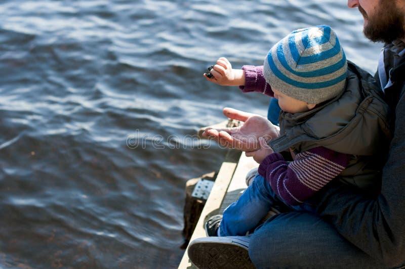 Pai e filho pequeno perto do rio imagens de stock royalty free