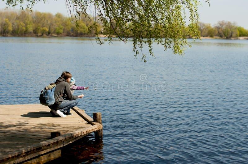 Pai e filho pequeno perto do rio imagem de stock
