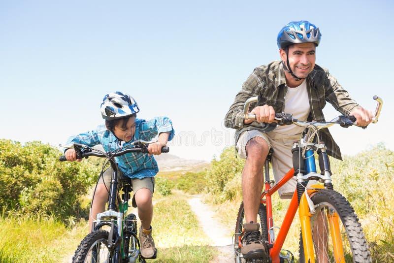 Pai e filho que biking através das montanhas imagens de stock royalty free