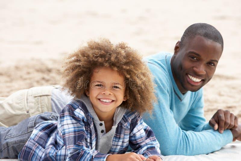 Pai e filho que colocam na praia imagens de stock