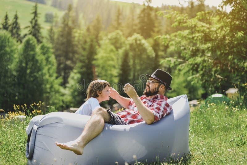 Pai e filho que descansam em um sofá do ar nas montanhas lamzac Curso fotos de stock royalty free