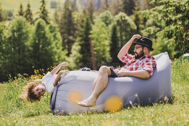 Pai e filho que descansam em um sofá do ar nas montanhas lamzac Curso foto de stock