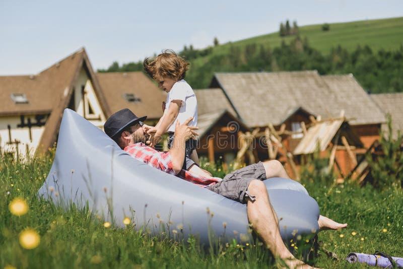 Pai e filho que descansam em um sofá do ar nas montanhas lamzac Curso fotografia de stock royalty free