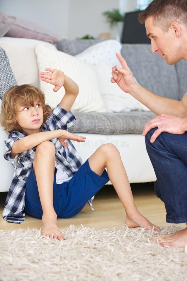 Pai e filho que discutem em casa fotos de stock royalty free
