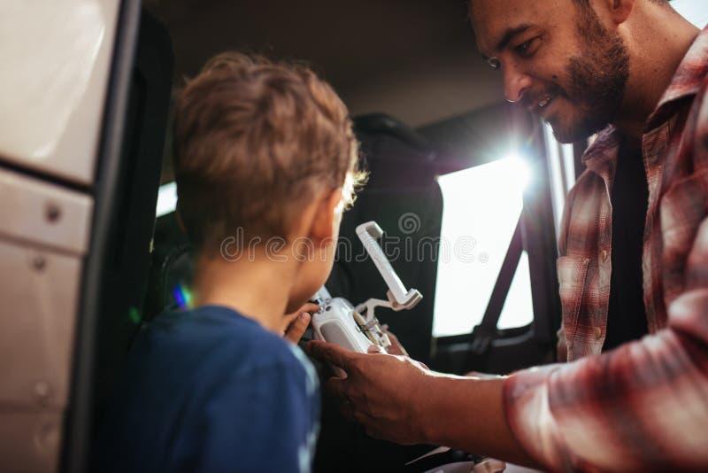 Pai e filho que estabelecem um zangão para voar imagem de stock