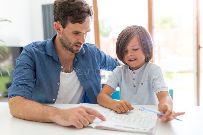 Pai e filho que fazem trabalhos de casa junto imagens de stock royalty free