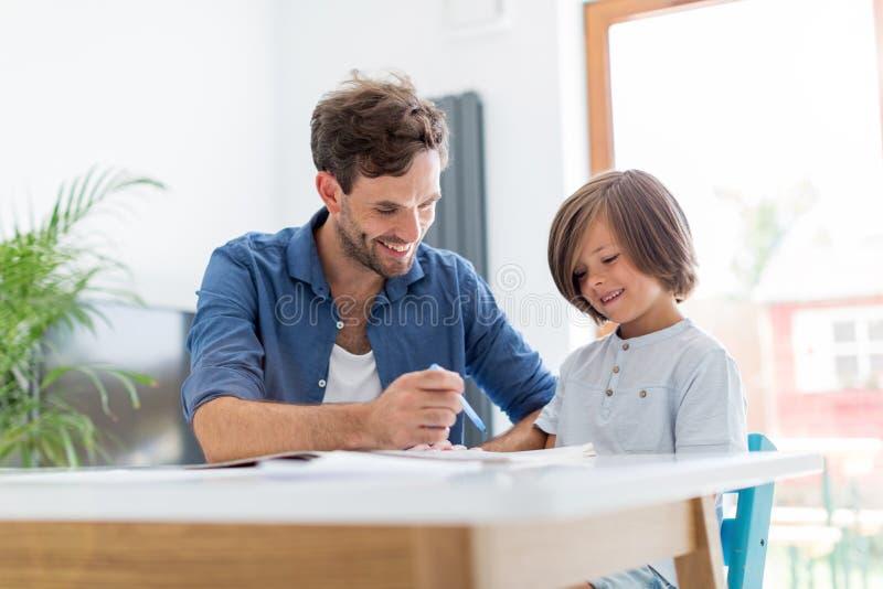 Pai e filho que fazem trabalhos de casa junto fotos de stock