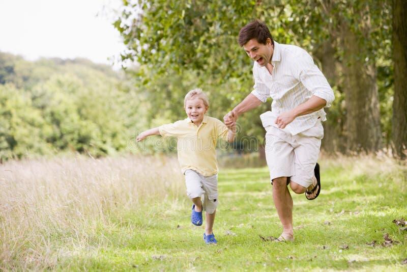 Pai e filho que funcionam nas mãos da terra arrendada do trajeto imagens de stock royalty free
