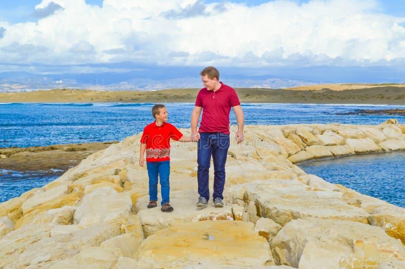 Pai e filho que guardam as mãos foto de stock