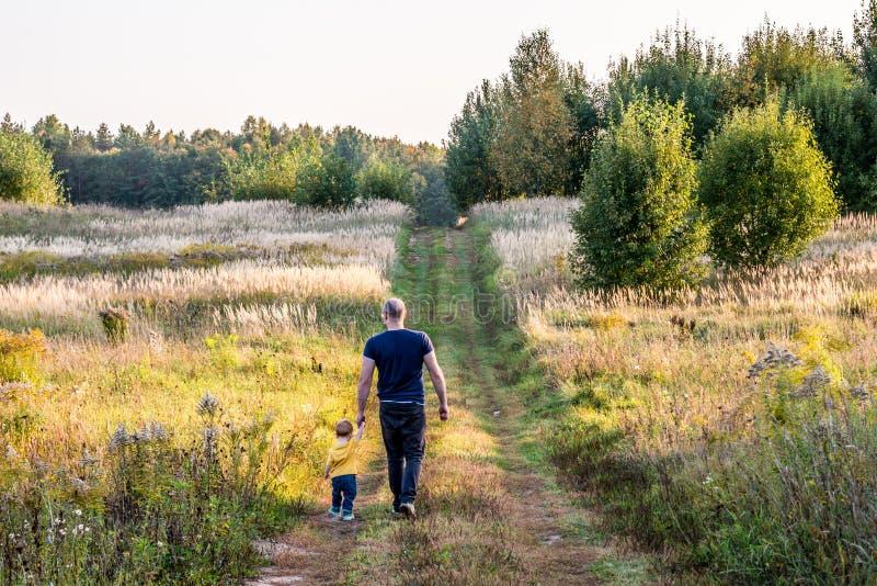 Pai e filho que guardam as mãos, andando junto fotos de stock royalty free