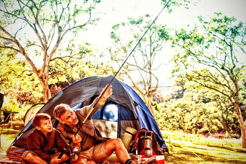 Pai e filho que guardam uma vara de pesca fora da barraca fotografia de stock