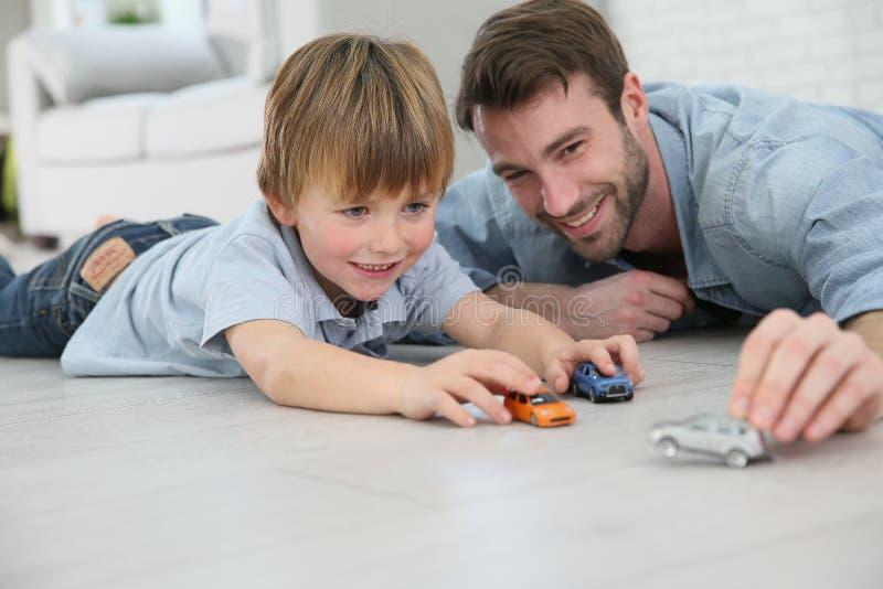 Pai e filho que jogam com carros do brinquedo fotos de stock royalty free