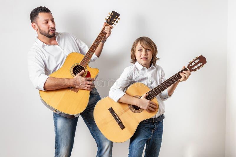 Pai e filho que jogam guitarra imagens de stock