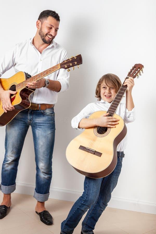 Pai e filho que jogam guitarra foto de stock