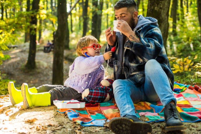 Pai e filho que jogam na floresta do outono que espirra o menino novo com o limpador do nariz entre árvores amarelas no parque Pa foto de stock