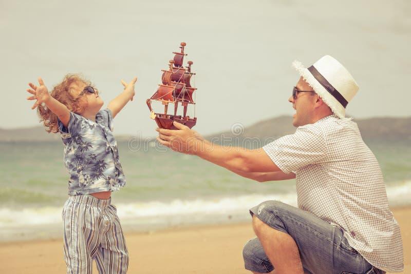 Pai e filho que jogam na praia no tempo do dia fotografia de stock