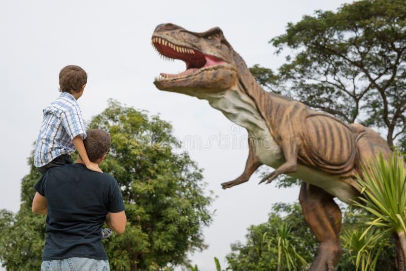 Pai e filho que jogam no parque de Dino da aventura imagem de stock royalty free