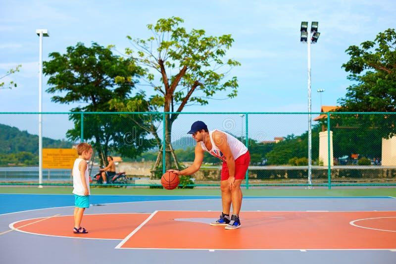 Pai e filho que jogam o basquetebol na terra de esporte foto de stock