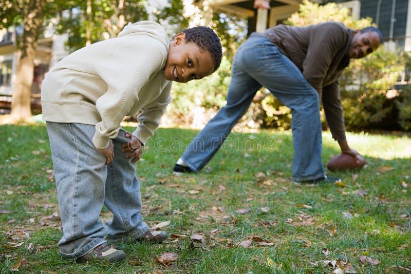 Pai e filho que jogam o futebol imagens de stock