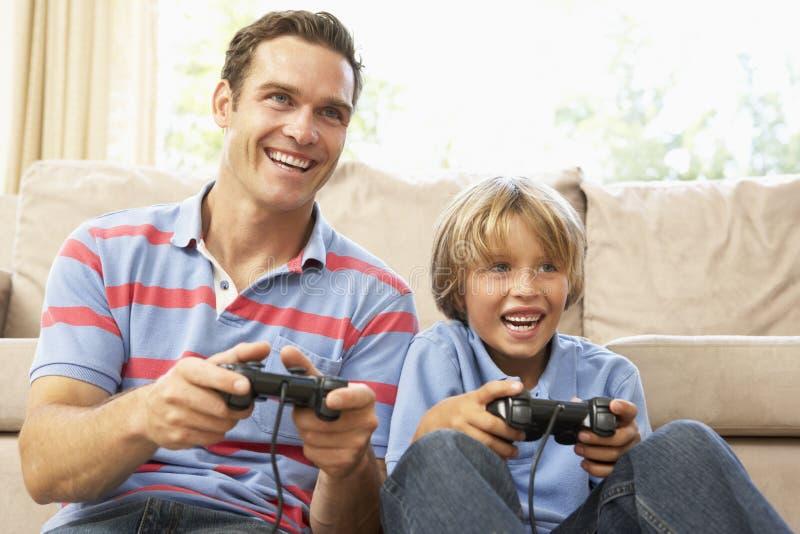 Pai e filho que jogam o jogo de computador fotos de stock