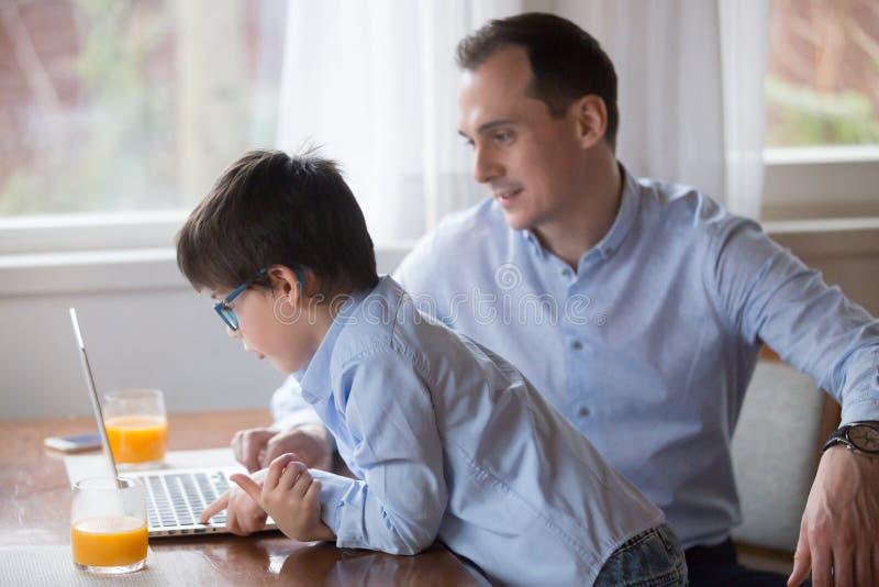 Pai e filho que jogam o jogo de computador no fim de semana em casa fotografia de stock royalty free