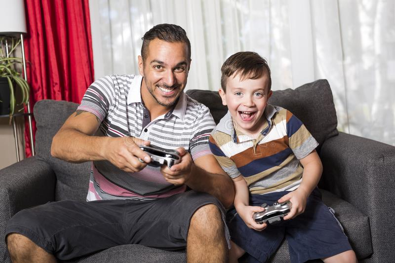 Pai e filho que jogam o jogo de vídeo fotos de stock