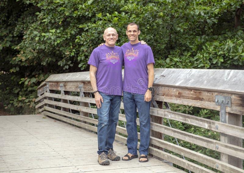 Pai e filho que levantam na ponte de madeira em Washington Park Arboretum, Seattle, Washington foto de stock
