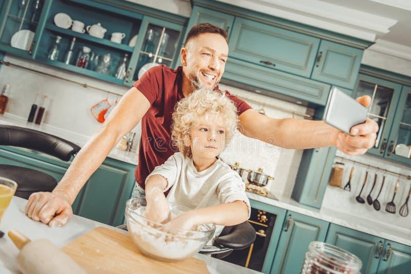 Pai e filho que levantam para o selfie ao fazer o café da manhã foto de stock