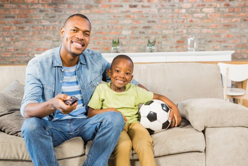 Pai e filho que olham a tevê junto no sofá fotografia de stock