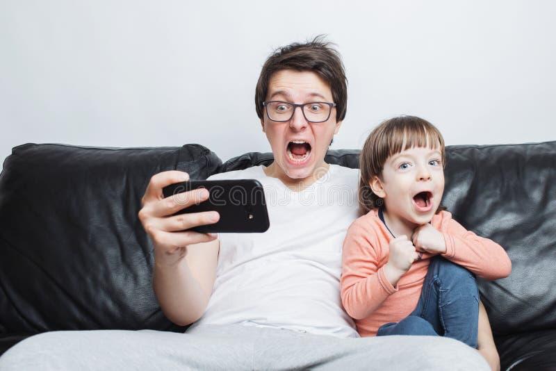 Pai e filho que olham um vídeo assustador no telefone que senta-se em um sofá em um fundo branco Estão gritando Um rapaz pequeno  imagens de stock royalty free