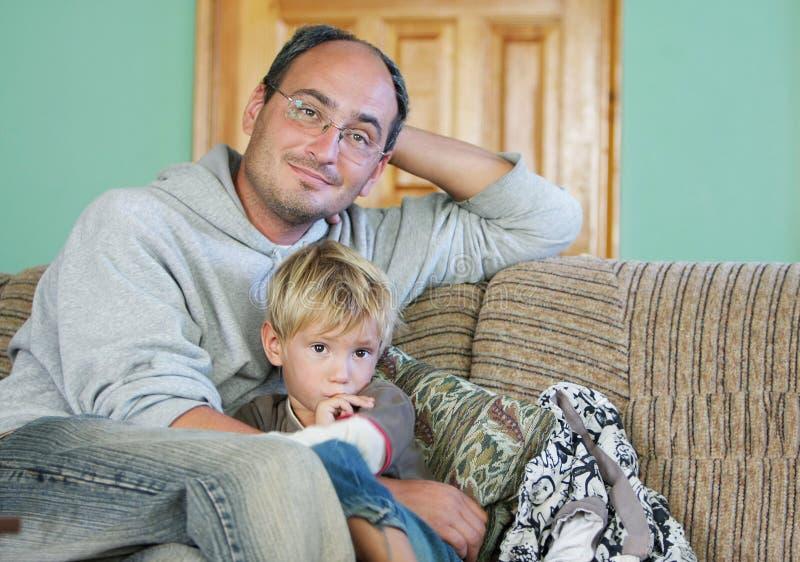 Pai e filho que prestam atenção à tevê fotografia de stock