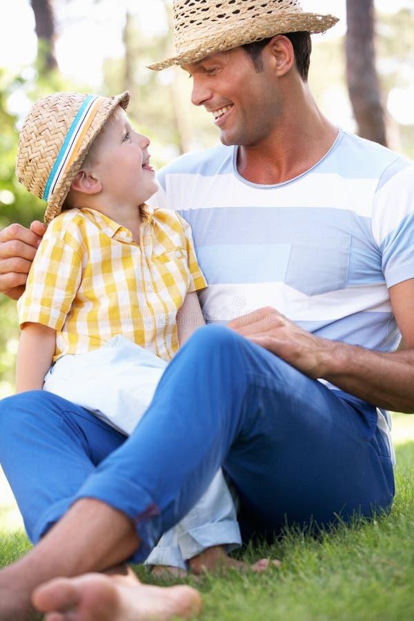 Pai e filho que relaxam no jardim do verão imagens de stock