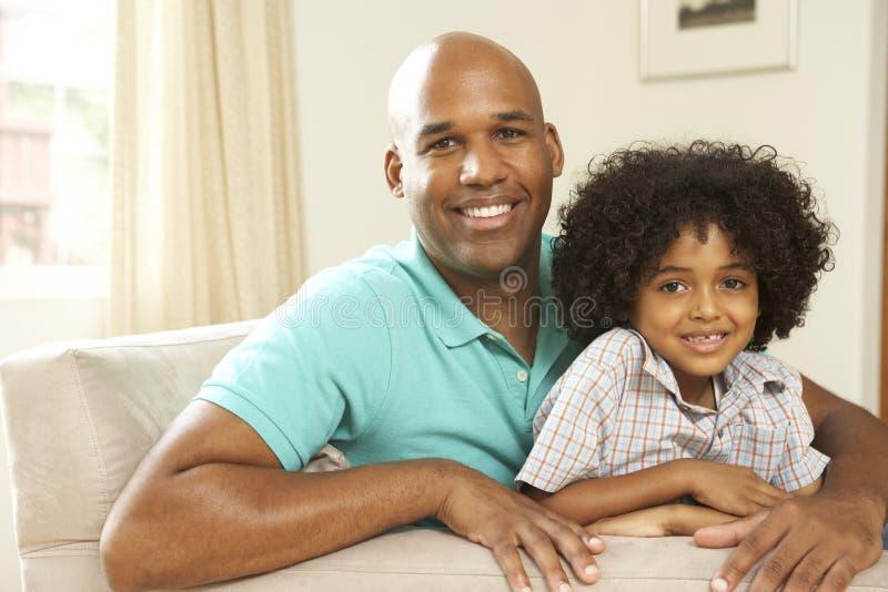Pai e filho que relaxam no sofá em casa fotografia de stock
