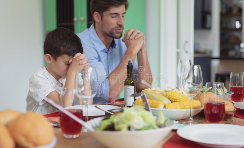 Pai e filho que rezam antes de ter o almoço na mesa de jantar imagens de stock royalty free