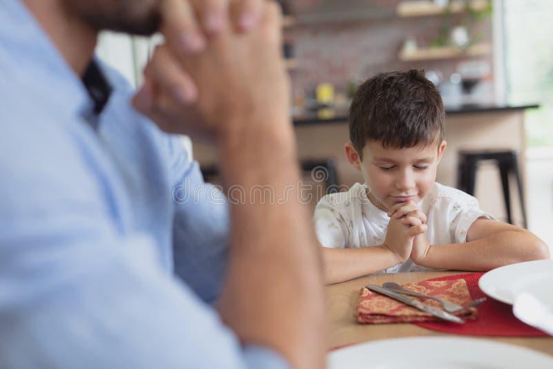 Pai e filho que rezam antes de ter o almoço na mesa de jantar imagens de stock