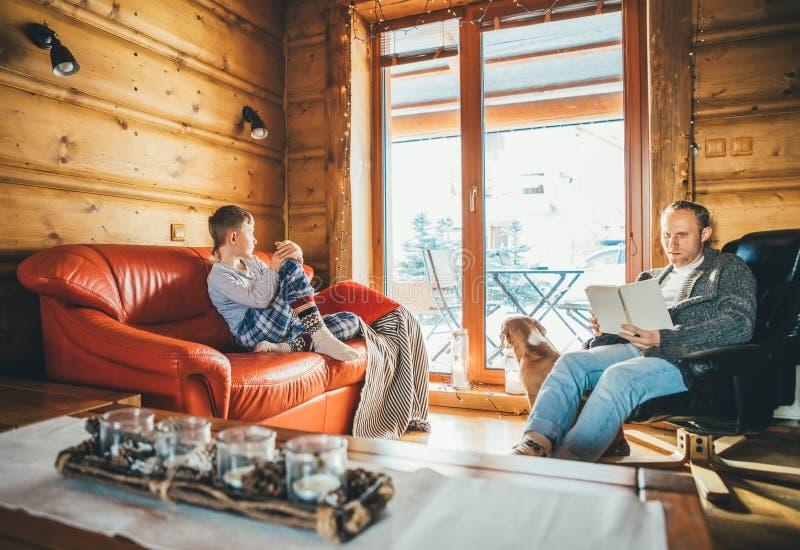 Pai e filho que sentam-se em sofás acolhedores na sala de visitas e na leitura Tempo do feriado da despesa da família na imagem d imagens de stock royalty free