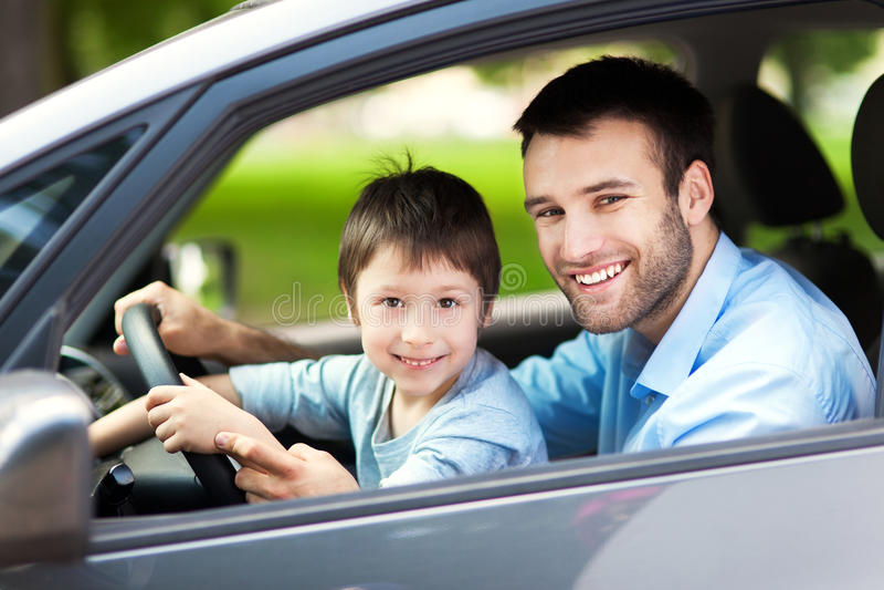 Pai e filho que sentam-se em um carro