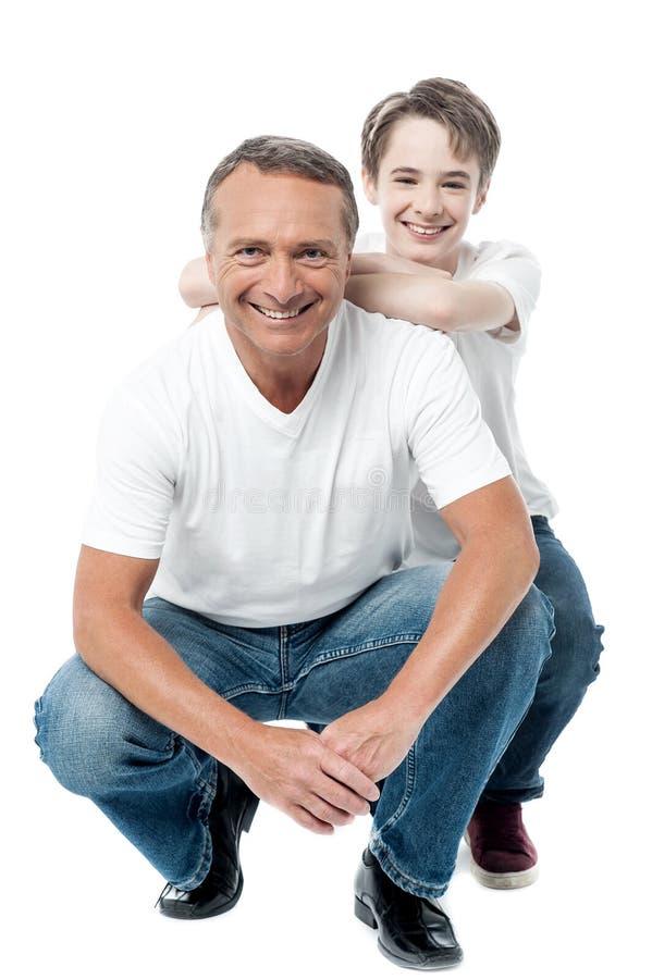 Pai e filho que sentam-se no assoalho imagens de stock