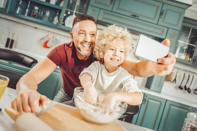 Pai e filho que sorriem amplamente ao fazer a foto junto imagens de stock