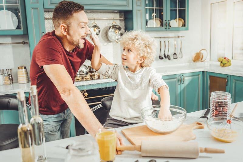 Pai e filho que têm muito divertimento ao cozinhar a torta junto fotos de stock royalty free